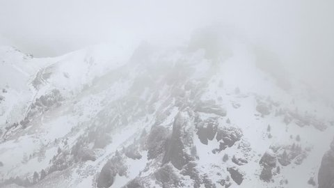 Aerial view. Flying backwards from rocky peak covered in snow. Cold winter foggy day in the mountains