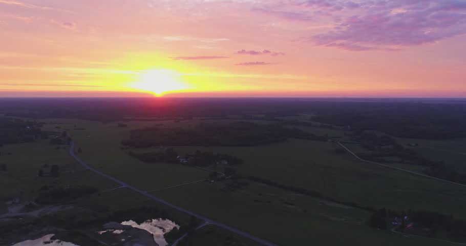 Amazing aerial view of beautiful sunset over the small country town. Green fields and tall trees. Nature / town landscape. | Shutterstock HD Video #1012592990