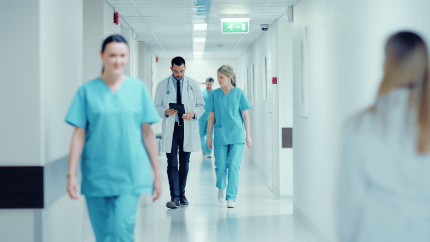 Surgeon and Female Doctor Walk Through Hospital Hallway, They Consult Digital Tablet Computer while Talking about Patient's Health. Modern Bright Hospital with Professional Staff. Shot on RED EPIC-W 8