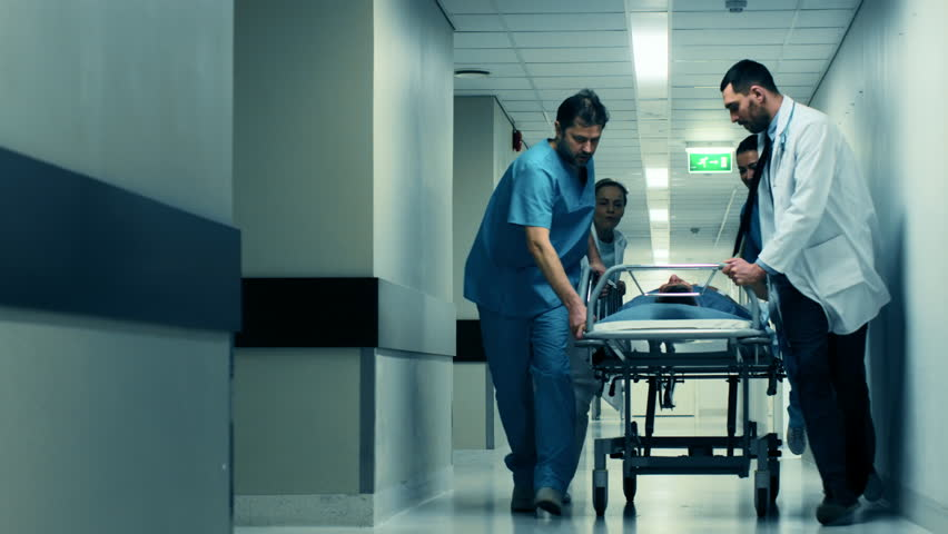 Emergency Department: Doctors, Nurses and Paramedics Push Gurney / Stretcher with Seriously Injured Patient towards the Operating Room. Shot on RED EPIC-W 8K Helium Cinema Camera. Royalty-Free Stock Footage #1012593887