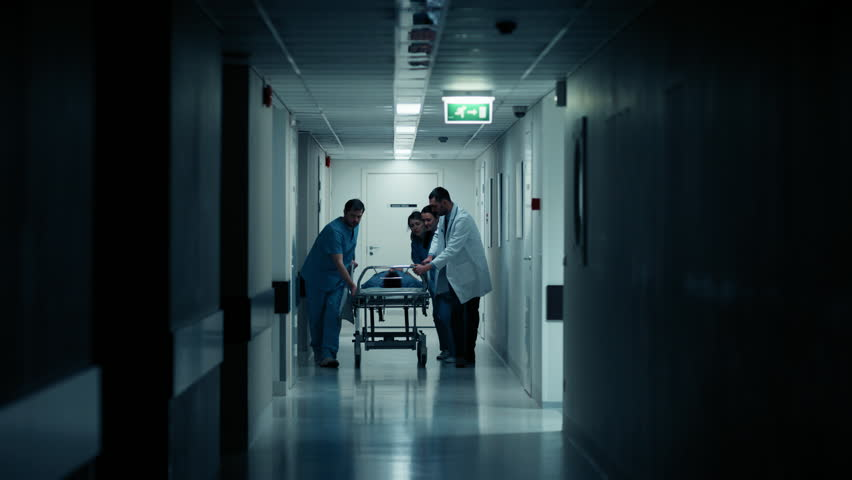 Emergency Department: Doctors, Nurses and Paramedics Run and Push Gurney / Stretcher with Seriously Injured Patient towards the Operating Room. Shot on RED EPIC-W 8K Helium Cinema Camera. | Shutterstock HD Video #1012593896
