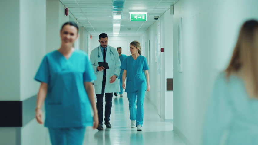 Female Surgeon and Female Doctor Walk Through Hospital Hallway, They Consult Digital Tablet Computer while Talking about Patient's Health.  Shot on RED EPIC-W 8K Helium Cinema Camera.