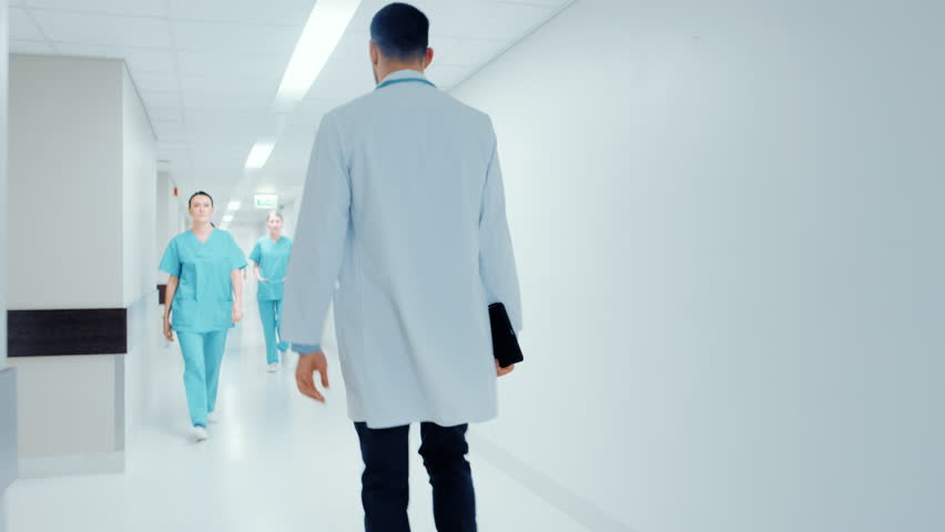 Following Back View Shot of a Doctor in a Hurry Walking Through Hospital Hallway. Greeting Nurses and His Colleagues. Bright Modern New Clinic. Shot on RED EPIC-W 8K Helium Cinema Camera.