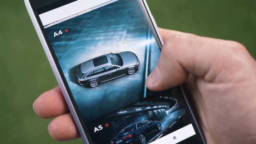 MONTREAL, CANADA - June 2018 : Shopping for a new luxury car online looking at different models on a smartphone mobile phone.
