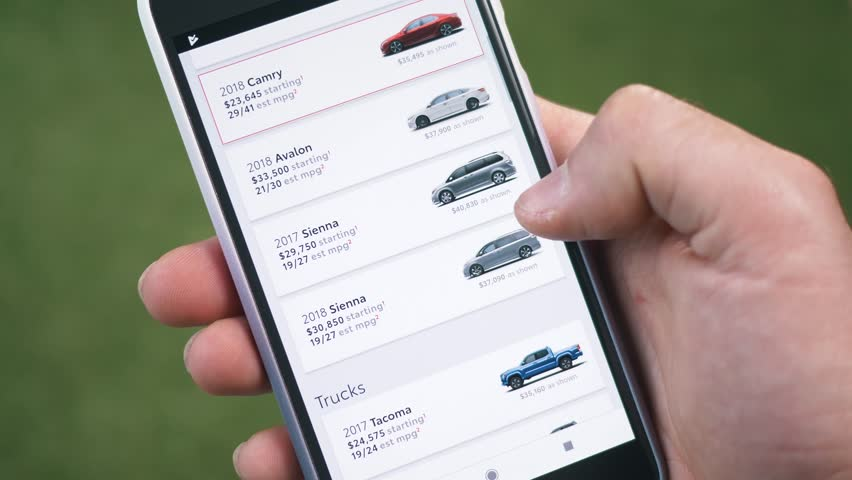 MONTREAL, CANADA - June 2018 :  for a new car online looking at different models on a smartphone mobile phone.