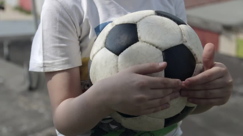 Young white boy holds a soccer ball in his hands in outdoor | Shutterstock HD Video #1012604873