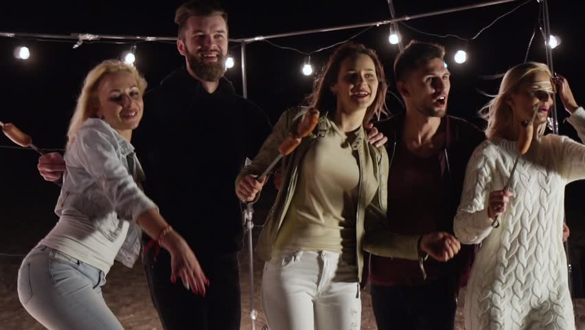 Young friends on a picnic dance and have fun on a night beach in slow motion | Shutterstock HD Video #1012629794
