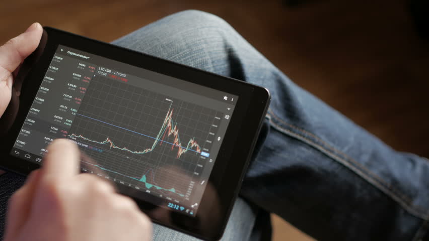 Stock market, trading online, trader working with tablet on stockmarket trading floor. Man touching screen, browse foreign exchange market data, chart. Forex. Crypto currency. Bitcoin cryptocurrency.