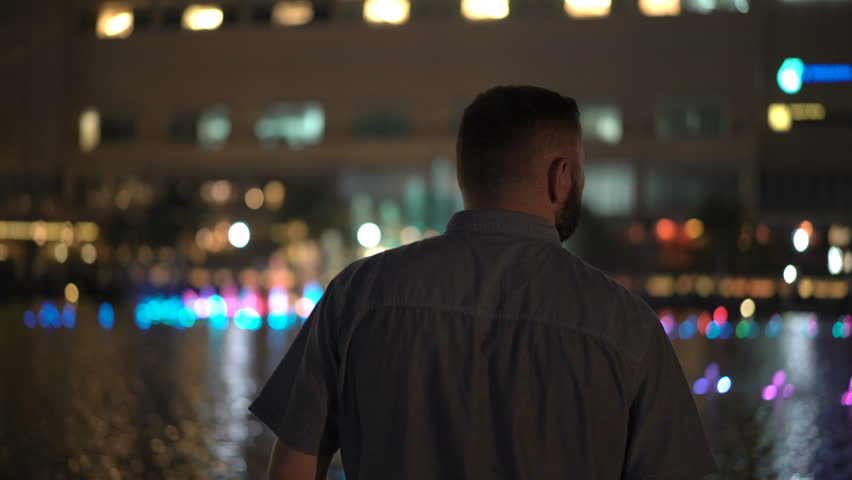 Young tourist man admire colorful fountain in the city at night    Shutterstock HD Video #1012642550