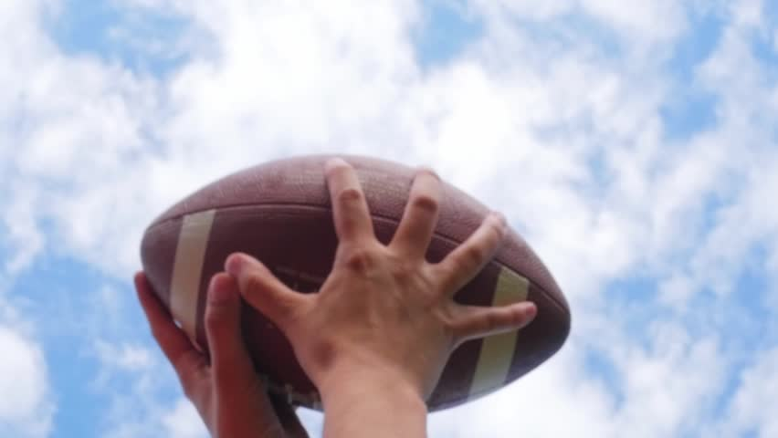 Hands catching rugby, football ball, slow motion