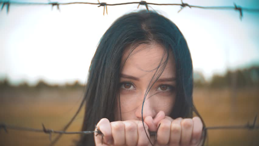 Girl brunette refugee behind barbed lifestyle wire camp slow motion video. the concept of freedom is upset Woman hands and barbed wire. girl Refugee, prison, refugees captivity concept