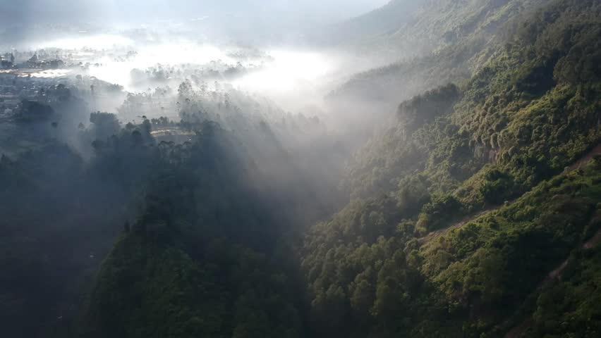 Aerial Clip of Foggy Valley Below A Mountain    Shutterstock HD Video #1012654709