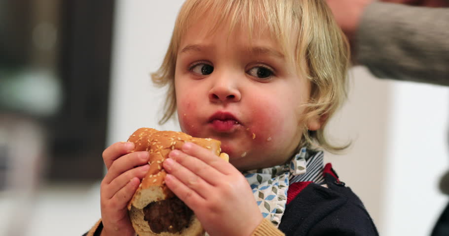 Child eating burger for dinner.  Toddler baby eats hamburger for the first time for supper