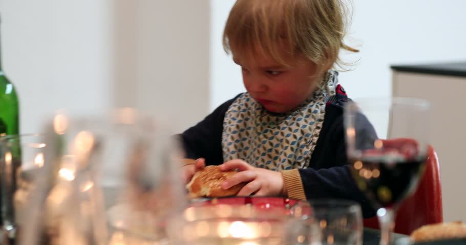 Baby toddler eating burger for dinner. Young boy eating hamburger for the first time for supper   Shutterstock HD Video #1012661489