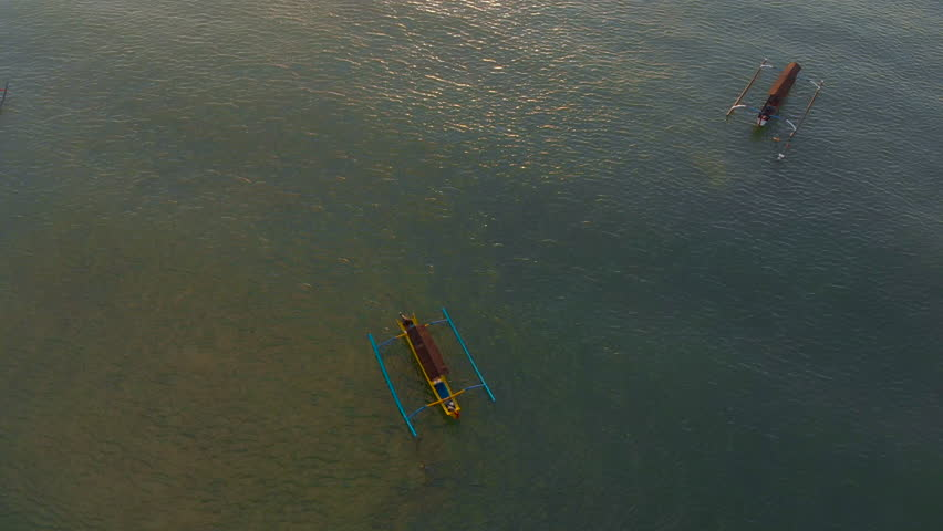 Aerial shot of three fisherman's boats in a sea at sunset time. Drone moves upwards