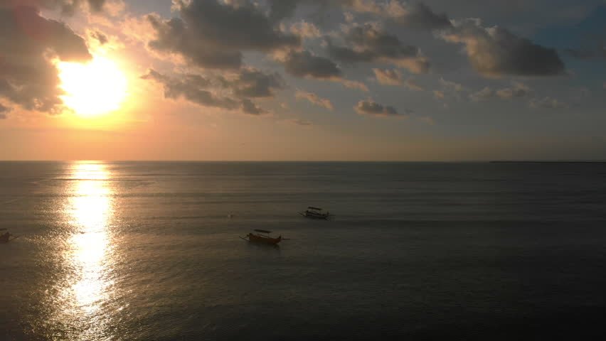 Aerial shot of three fisherman's boats in a sea at sunset time. Drone moves to the right