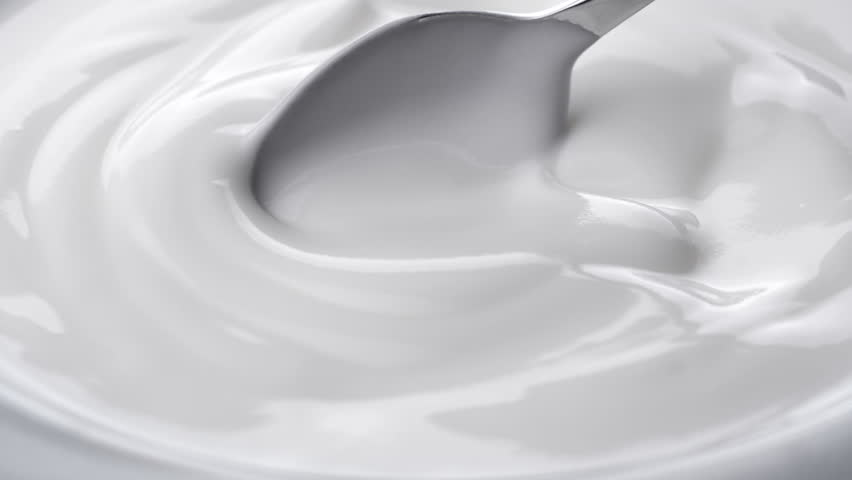 Closeup shot of mixing yogurt with spoon, Rotating  #1012670081