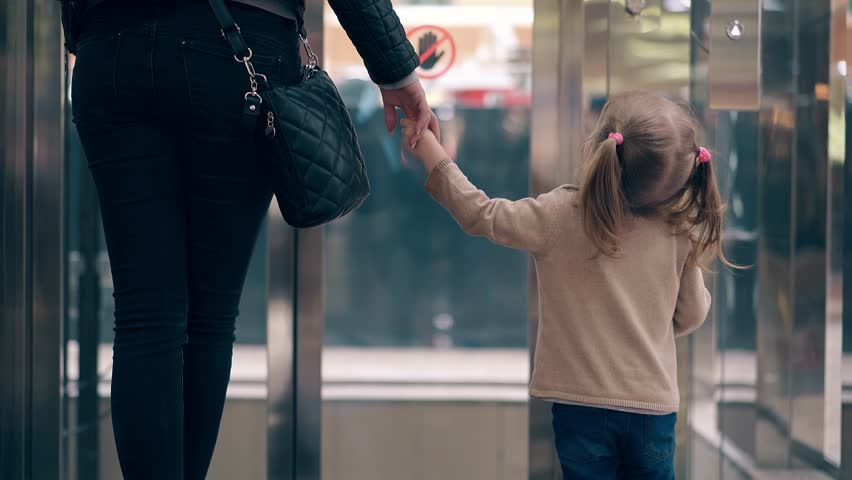 CU, 4k: Young mother leads her daughter by the hand, along the business center. They enter the elevator.