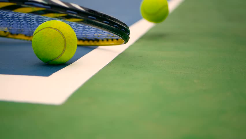 Close up of tennis equipment on the court. Sport, recreation concept. Yellow racket with a tennis ball in motion on a clay green blue court next to the white line with copy space and soft focus. #1012707275