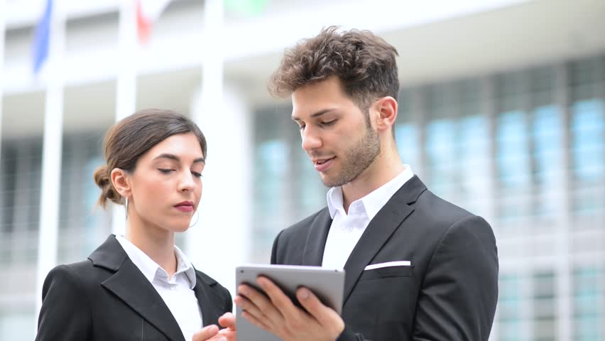 Couple of business people using a tablet outdoor | Shutterstock HD Video #1012708640