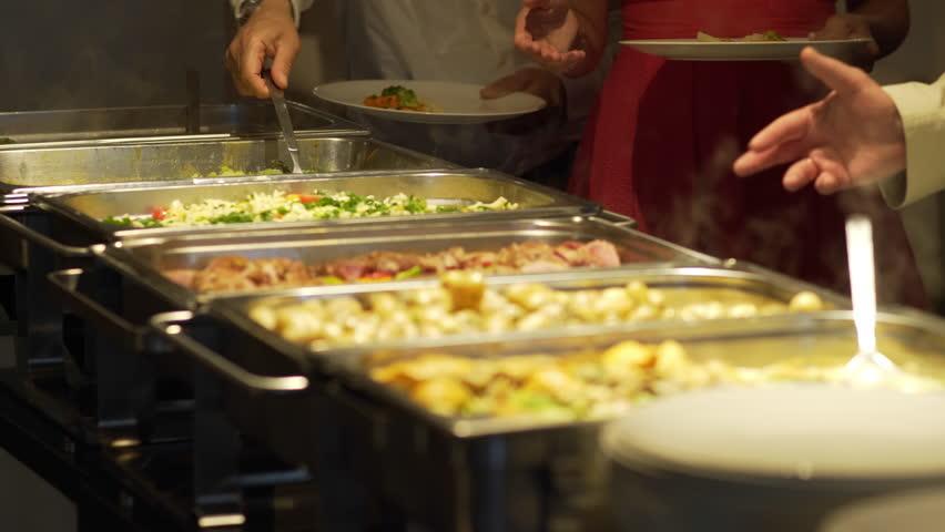 Restaurant guests select food from a buffet.   Shutterstock HD Video #1012710962