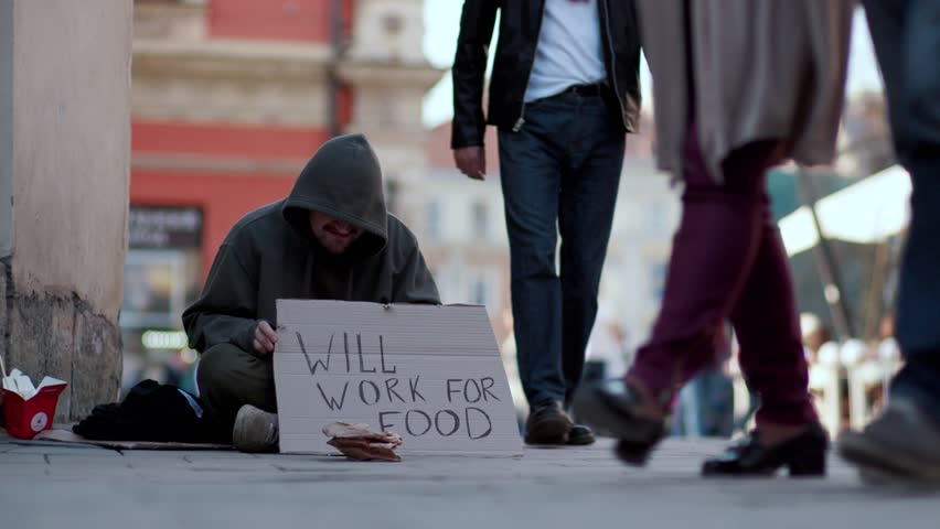 Homeless man sitting on a street with sign people walk around honeliness sad social cardboard homeless beggar poverty poor hungry dirty unemployed despair male slow motion