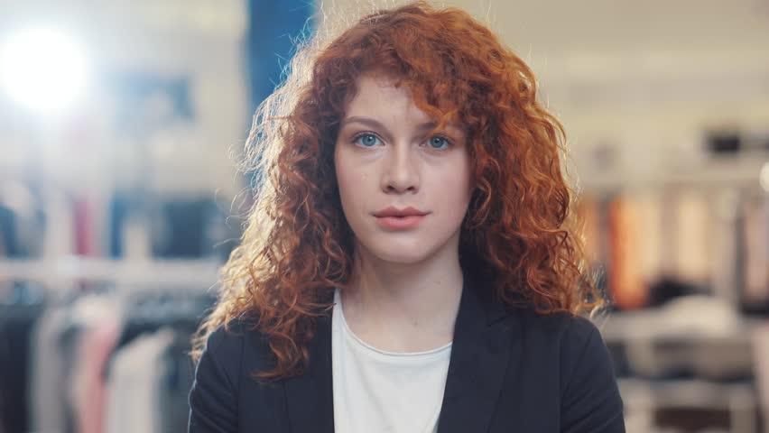 Portrait of red curly hair young woman look at camera at clothes store design girl shopping face spring customer light happy indoors female retail beautiful lifestyle pretty young adult cute lady #1012720193