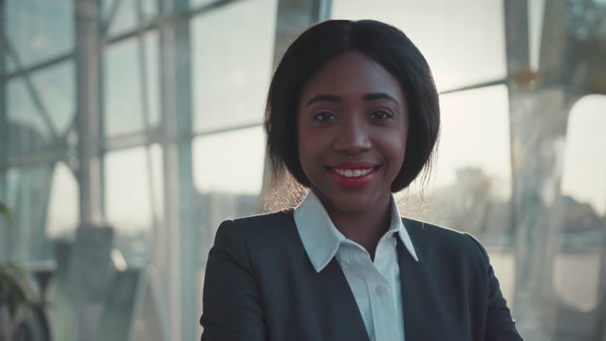 Gorgeous beautiful Afro-American woman in a stylish suit cutely smiling straight to camera. | Shutterstock HD Video #1012720232