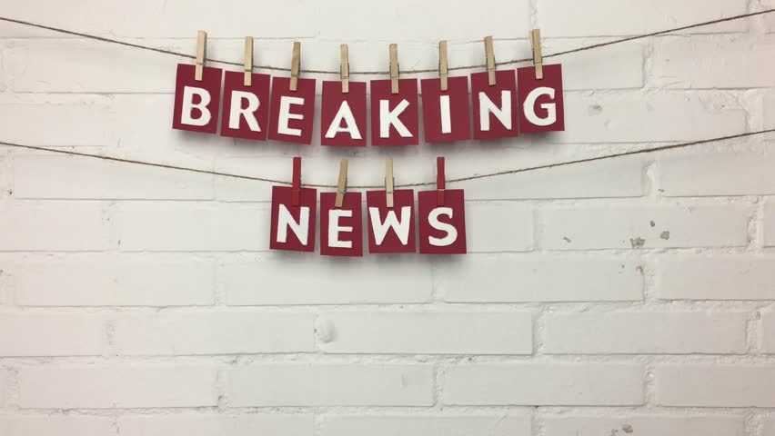 """Phrase """"breaking news on a rope with pincers, on the bottom of bricks. 