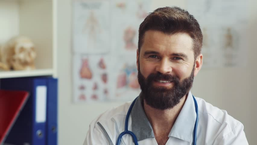 One good-looking doctor with brown hair looking at camera at clinic. Kind positive Caucasian physician with amicable smile. Indoors. Close-up. | Shutterstock HD Video #1012721057