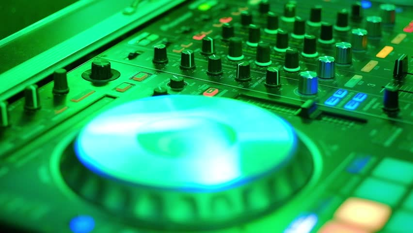 Static HD video Dj mixes the track in the nightclub at party. Closeup on the DJ's mixer filled with green light.