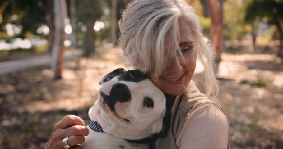 Happy mature female pet owner relaxing and embracing dog in the countryside in spring