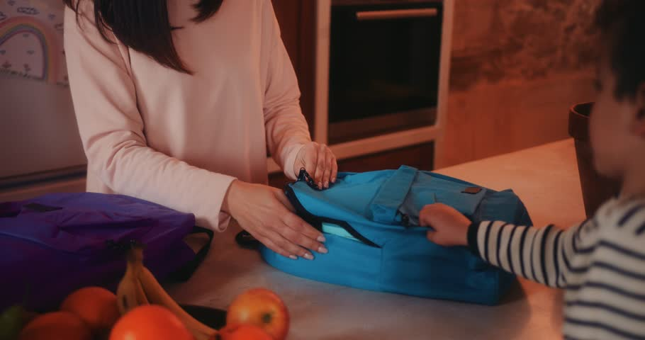 Close-up of mother packing school bags with lunch boxes and healthy food for children