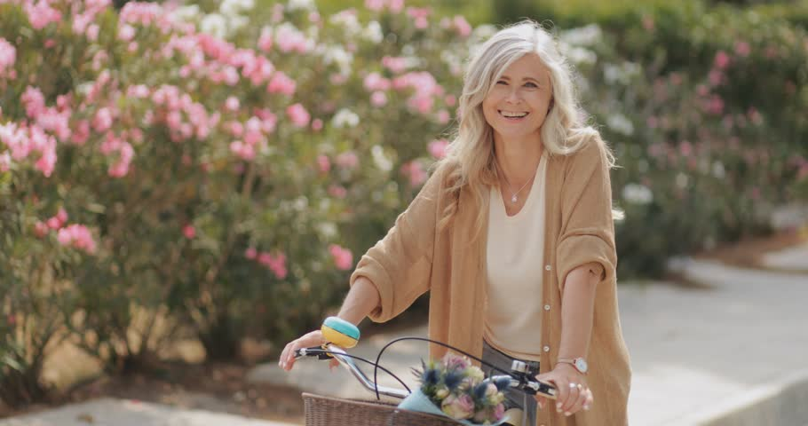 Happy mature woman having fun cycling with vintage bicycle on sunny day in spring