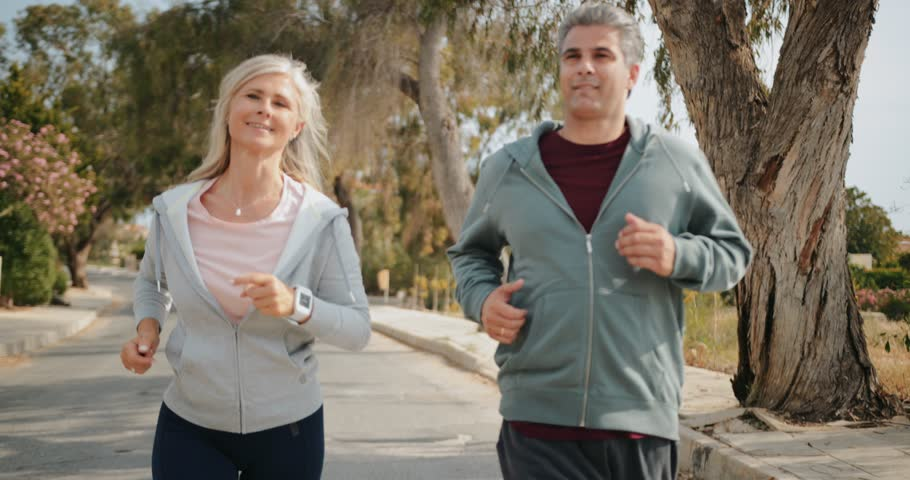 Active senior husband and wife having fun doing cardio exercise and running together outdoors Royalty-Free Stock Footage #1012743770