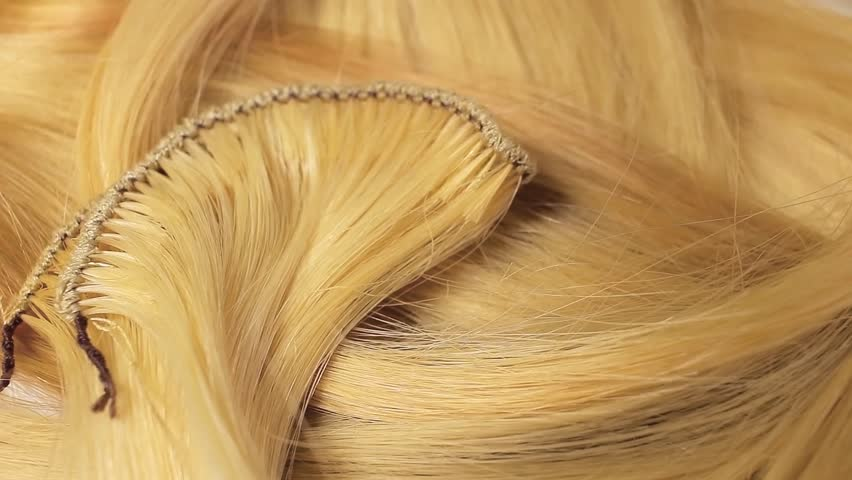 Hair extension cutted hair fibers blonde weft rotating pattern macro texture background backdrop footage video. #1012748084