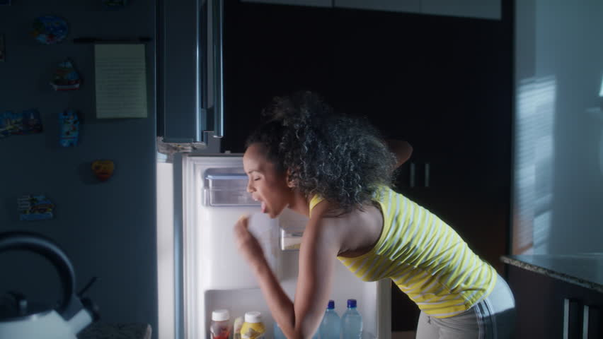 African american woman doing midnight snack at home. She eats a sandwich and looks for food into the refrigerator at night. | Shutterstock HD Video #1012750520