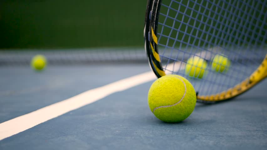 Close up of tennis equipment on the court. Sport, recreation concept. Yellow racket with a tennis ball in motion on a clay green blue court next to the white line with copy space and soft focus. #1012758356