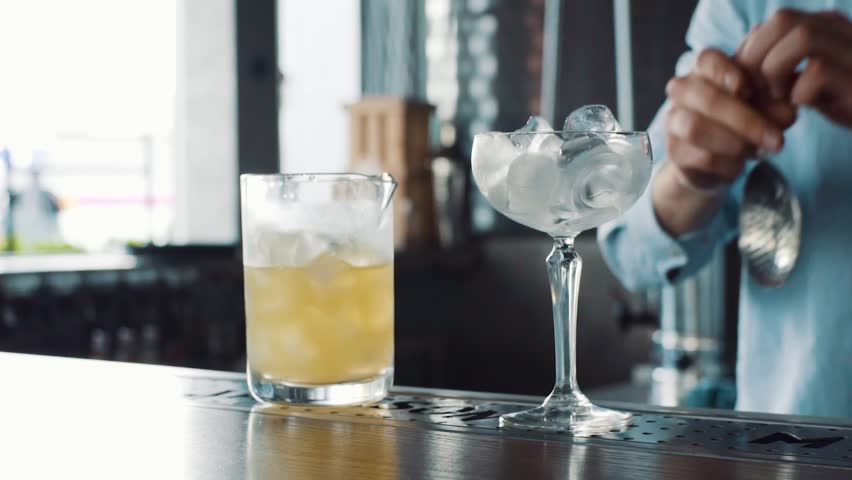 Closeup of bartender pouring drink into the glass