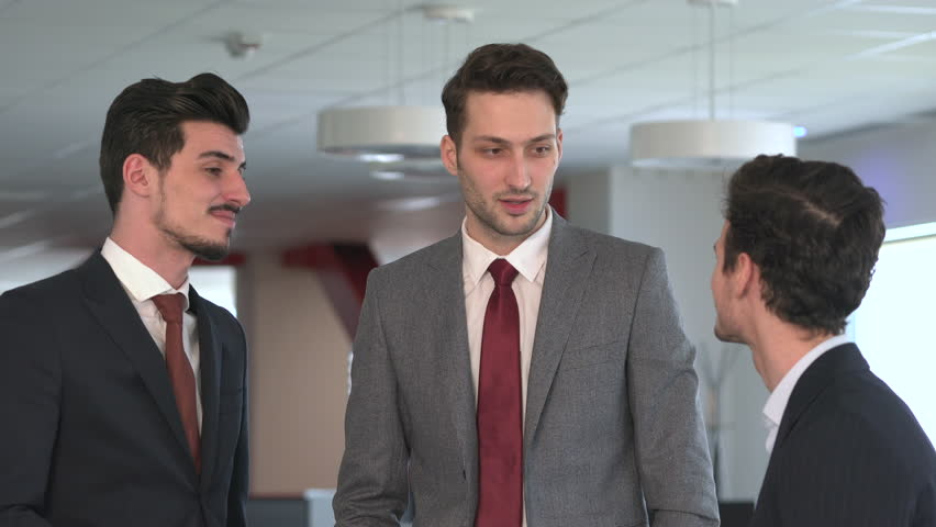 Three young businessmen talking and smiling. #1012765502