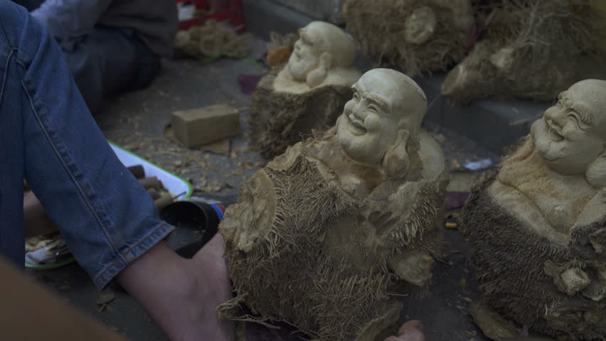 Making Buddha figurines from a tree with a chisel