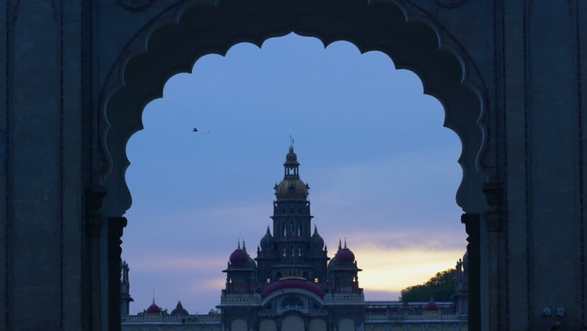 Evening view of birds flying over Mysore palace through the entrance gate