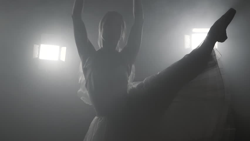 Professional ballerina dancing ballet in spotlights on stage. Beautiful caucasian young girl wearing white tutu dress. Black and white vintage retro effect tonned. Slow motion #1012798649