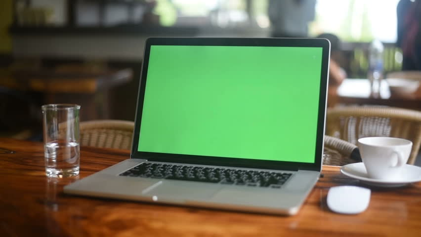 A laptop computer with a key green screen set on coffee shop. #1012807247