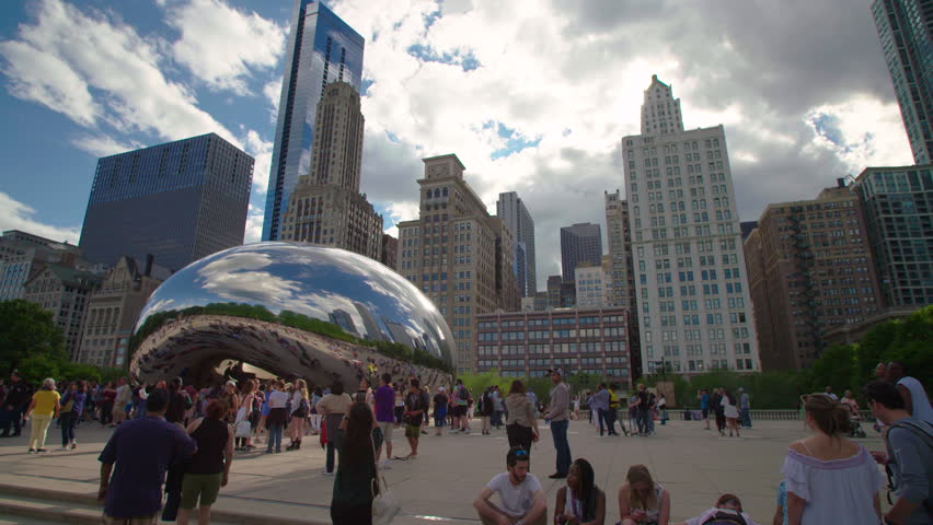 CHICAGO, USA - JUNE 25 20137 People walking around the famous Chicago Cloud Gate, The Bean Sculpture, with the Chicago skyline in the background. | Shutterstock HD Video #1012812407