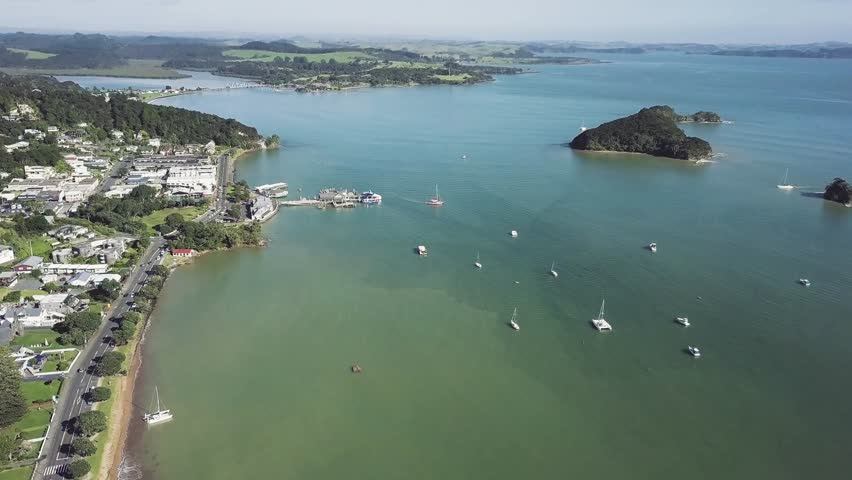 Aerial, Paihia New Zealand in the bay of islands. Morning high angle shot of ocean with ferry wharf in small town. | Shutterstock HD Video #1012827467
