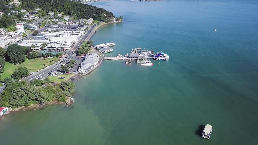 Aerial, pull back view of Paihia ferry wharf, popular tourist spot in the New Zealand bay of islands. | Shutterstock HD Video #1012829111