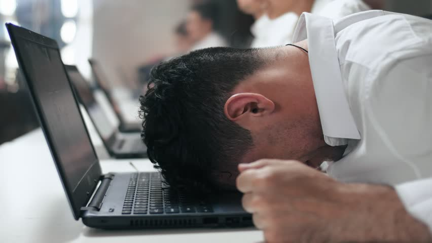 Overwhelmed stressed employee feeling angry at work in office. Close-up of worker tired on his hated work.