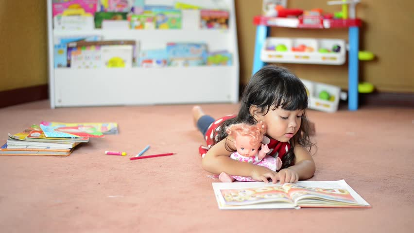 A cute little child Asian girl doing homework and reading a book. Kid enjoy learning with happiness at home. Clever,Education and smart learning concept