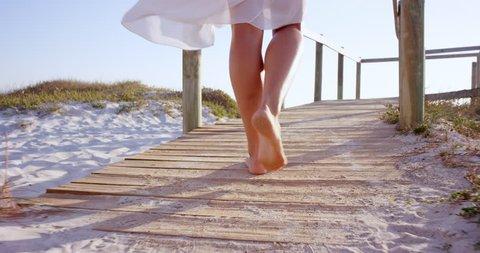 Beautiful woman wearing white dress walking on wooden beach walkway at sunset
